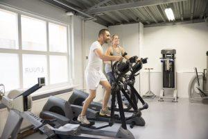 Een foto in de oefenzaal van fysiotherapiepraktijk PUUR. Waarbij twee klanten op de crosstrainer staan.