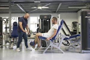 De fysiotherapeut begeleid een klant die op de leg extension een oefeing uitvoert.