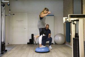 De fysio begeleid een stabiliteits oefening op de bosu bal. De klant voert een één benige oefening uit.