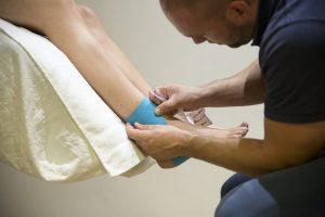 Een fysio therapeutischebehandeling bij fysiotherapiepraktijk PUUR. Waarbij sportfysiotherapeut Sven de enkel intaped. Hij gebruikt hiervoor kinesiotape in plaar van wit sporttape.