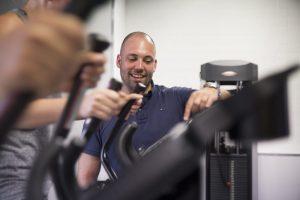 Sportfysiotherapeut Sven stelt de crosstrainers in.