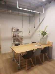 De wachtkamer van fysiotherapiepraktijk PUUR. Met een steigerbuis houten tafel met Scandinavische kuipstoeltjes.