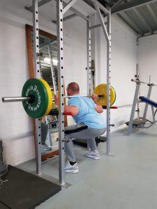 De sportfysiotherapeut van fysiotherapiepraktijk PUUR, staat in diepe hurkhouding met een barbell in zijn nek. De eindstand van de sqaute oefening.